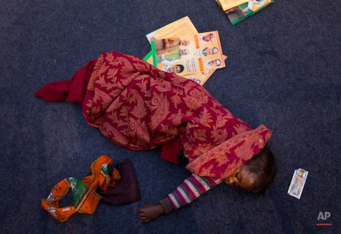 An infant sleeps on a carpet at the rally area where Indian Prime Minister Narendra Modi is addressing an election campaign rally ahead of Delhi state election in New Delhi, India, Wednesday, Feb. 4, 2015. Delhi goes to the polls on Feb. 7. (AP Photo/Saurabh Das)
