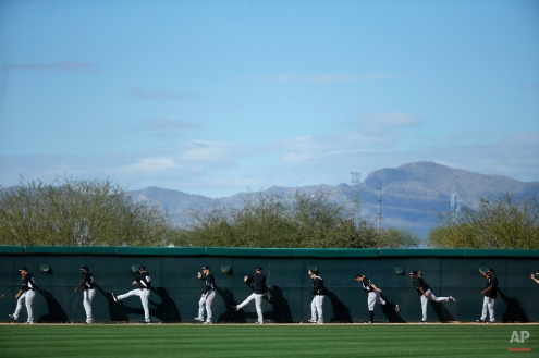 Chicago White Sox players warm up before a spring training baseball workout Tuesday, Feb. 24, 2015, in Phoenix. (AP Photo/John Locher)