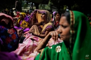 Anganwadi, or government-sponsored mother and child care, workers listen to a speaker during a protest in New Delhi, India, Thursday, Feb. 19, 2015. The workers demanded that they be recognized as government employees and their salaries increased. (AP Photo/Altaf Qadri)