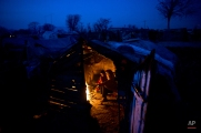 Pakistani Sughar Ramadan, 38, and her daughters Shameem, 7 and Samreen, 2, sit around a fire to warm themselves from the night cold inside their makeshift home in a slum in Islamabad, Pakistan, Friday, Feb. 13, 2015. (AP Photo/Muhammed Muheisen)