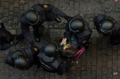 Riot police drag an activist from blocking the door to stop Jessica Bernice Michelena and her family's eviction together in Madrid, Spain, Tuesday, Feb. 3, 2015. Jessica, 40 years old, and her partner, Eduardo Lucas Zambrano, 37 years old, unemployed and their children: Miguel Angel, 7, Ana Mile Lucas, 5, occupied an apartment 5 months ago after she lost her job, was evicted from a previous place and lived in the street with her children for 15 days. With her only income of euros 350 ($397) from a part time cleaning job she can not afford to pay rent and she barely can buy food. The eviction was carry out in spite dozens of housing right activists tried to stop it. (AP Photo/Andres Kudacki)
