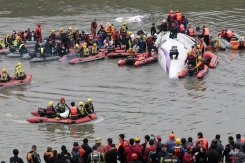 Emergency personnel use a dinghy to bring the body of a passenger in a commercial plane crash to the river shore as others crowd around the plane to rescue other passengers in Taipei, Taiwan, Wednesday, Feb. 4, 2015. The Taiwanese commercial flight with 58 people aboard clipped a bridge shortly after takeoff and crashed into a river in the island's capital on Wednesday morning. (AP Photo/Wally Santana)