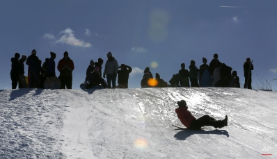 Sledding enthusiasts are silhouetted against the sky as they wait for their turn on a snow covered hill near Soldier Field Monday, Feb. 2, 2015, in Chicago. The National Weather Service says Chicago saw 19.3 inches of snow after the Sunday storm. Schools were canceled in Chicago and across the metro area on Monday. (AP Photo/Charles Rex Arbogast)