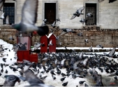 A man selling food for pigeons sits in a cubicle, near Yeni Cami, in Istanbul, Turkey, Thursday, Feb. 19, 2015. Turkey's largest city, Istanbul, has been hit by a storm that has dumped up to a 60 centimeters (24 inches) of snow in some areas since Tuesday, wreaking havoc on roads. (AP Photo/Emrah Gurel)