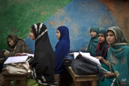 Afghan refugee schoolgirls attend a class at a makeshift school on the outskirts of Islamabad, Pakistan, Monday, Feb. 23, 2015. (AP Photo/Muhammed Muheisen)