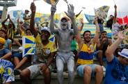 Fans of the Unidos da Tijuca samba school cheer before the announcement of the winner of the Carnival samba school contest at the Sambadrome in Rio de Janeiro, Brazil, Wednesday, Feb. 18, 2015. (AP Photo/Leo Correa)