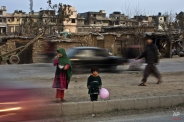 An Afghan refugee child holds a balloon as she and her sister wait on a street median to cross on the outskirts of Islamabad, Pakistan, Wednesday, Feb. 18, 2015. (AP Photo/Muhammed Muheisen)