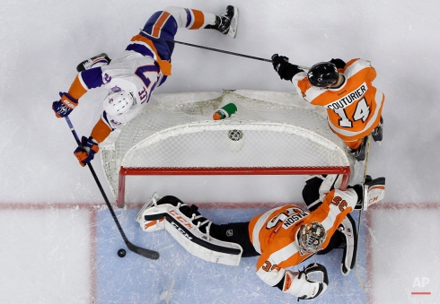 New York Islanders' Anders Lee (27) tries to score past Philadelphia Flyers' Steve Mason (35) and Sean Couturier (14) during the third period of an NHL hockey game, Thursday, Feb. 5, 2015, in Philadelphia. (AP Photo/Matt Slocum)