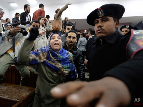 """Mother of Egyptian Moustafa Yousri shouts against the court after her son was sentenced among 21 people, including prominent activists to prison terms over an unauthorized street protest in 2013, at a Cairo court, Egypt, Monday, Feb. 23, 2015. An Egyptian court sentenced Alaa Abd el-Fattah, an icon of the country's 2011 revolt to five years in prison Monday, showing authorities' determination to continue to stifle dissent despite promises by its president to release """"wrongly jailed youths."""" Another defendant, Ahmed Abdel Rahman, was also given five years. The others were sentenced to three years. (AP Photo/Amr Nabil)"""