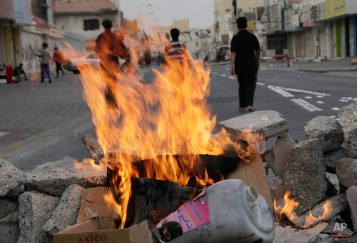 Bahraini children play in a street behind burning debris used as a roadblock ahead of an anti-government protest Thursday, Feb. 12, 2015, in the western village of Malkiya, Bahrain. Many shops in opposition areas nationwide were closed Thursday, the first day of a three-day general strike called by the February 14 opposition youth group before Saturday's fourth anniversary of Bahrain's pro-democracy uprising. Youths blocked roads in many areas, enforcing the strike and attempting to slow down police vehicles. (AP Photo/Hasan Jamali)