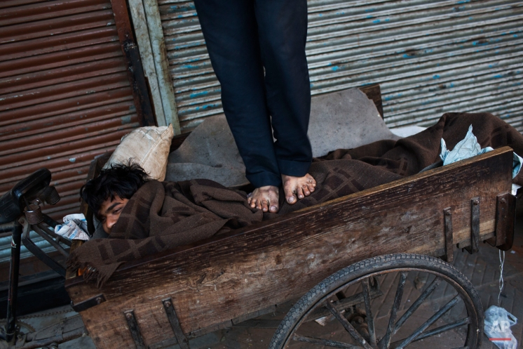 An Indian homeless man gets a massage from a friend early in the morning at the old city area of New Delhi, India, Friday, Feb. 27, 2015. Old Delhi despite of being extremely crowded and dilapidated still serves as the symbolic heart of the city. (AP Photo/Bernat Armangue)