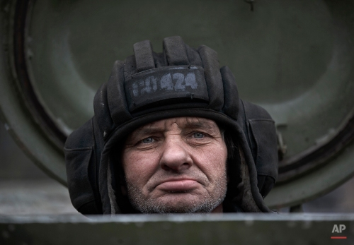 A Russia-backed separatist fighter sits in a self propelled 152 mm artillery piece, part of a unit moved away from the front lines, in Yelenovka, near Donetsk, Ukraine, Thursday, Feb. 26, 2015. (AP Photo/Vadim Ghirda)
