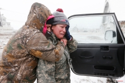 Taylor Millar, left, hugs her friend Jennifer Bruno, after Bruno was forced to vacate her house when it was heavily damaged by ocean waves in a winter storm, Tuesday, Jan. 27, 2015, in Marshfield, Mass. The storm has punched out a section of the seawall in the coastal town of Marshfield, police said. (AP Photo/Michael Dwyer)