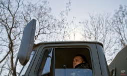 A Russia-backed rebel sits in the cabin of a tow-truck part of a convoy transporting artillery pieces, outside the city of Donetsk, Ukraine, Tuesday, Feb. 24, 2015. Howitzers were seen moving east Tuesday from the largest rebel-held city in eastern Ukraine further into separatist-controlled territory, but the Ukrainian government disputed the rebels' claim that a heavy weapons pullback had begun. (AP Photo/Vadim Ghirda)