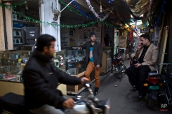 In this Sunday, Jan. 11, 2015 photo, Pakistani Waseem Akram, 27, center, stands by the mobile shop where he works at a market in Rawalpindi, Pakistan. By day, Akram sells mobile phone accessories from an alleyway shop in an old neighborhood of this Pakistani city. But by night, he stands before a mirror, shaving away his beard and picking through mascara and rouge to become Rani, a female wedding party dancer. (AP Photo/Muhammed Muheisen)