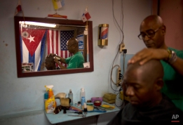 Eugenio Lafargue cuts a client's hair inside his barbershop decorated with a Cuban and U.S. flag in Havana, Cuba, Friday, Feb. 27, 2015. The U.S. and Cuba held a second round of negotiations Friday in Washington on restoring diplomatic relations after a half-century interruption, although an immediate breakthrough appeared unlikely. (AP Photo/Ramon Espinosa)