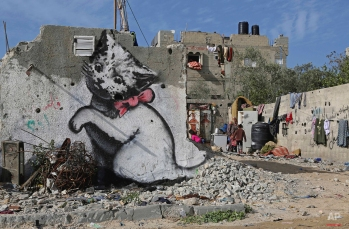 A Palestinian woman works with her children near a mural of a playful-looking kitten, presumably painted by British street graffiti artist Banksy, is seen on a wall of destroyed which was destroyed in last summer's Israel-Hamas war, in Beit Hanoun, in the northern Gaza Strip, Friday, Feb. 27, 2015. In a short film posted on his website, the popular street artist appears to sneak into Gaza through an underground tunnel from Egypt. The video shows aftermath footage from the 2014 Gaza summer war and includes political commentary about the stripís misery. Some of his work is seen as well, such as a drawing of a Greek goddess cowering against a remaining concrete slab of a destroyed structure. (AP Photo/Adel Hana)