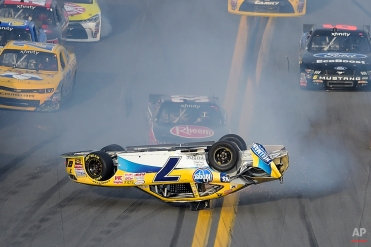 Regan Smith (7) flips on the front stretch after being involved in a multi-car accident during a NASCAR Xfinity series auto race at Daytona International Speedway, Saturday, Feb. 21, 2015, in Daytona Beach, Fla.(AP Photo/Phelan M. Ebenhack)