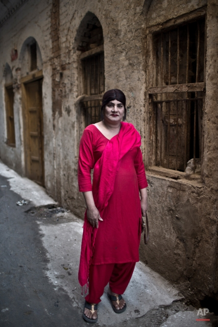 In this Thursday, Jan. 8, 2015 photo, Pakistani Bakhtawar Ijaz, 43, poses for a picture in an alley of a neighborhood in Rawalpindi, Pakistan. Across conservative Pakistan, where Islamic extremists launch near-daily attacks and many follow a strict interpretation of their Muslim faith, those like Bakhtawar face a challenge of balancing two identities. Some left their villages for the anonymity of a big city, fearing the reactions of their families while still concealing identity from neighbors and co-workers. (AP Photo/Muhammed Muheisen)