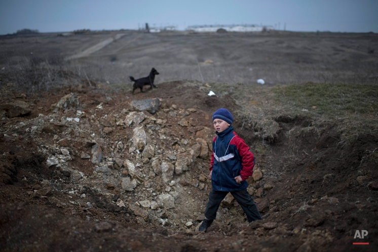 A boy stands in a crater from an explosion in the village of Chermalyk, eastern Ukraine, Thursday, Feb. 26, 2015. In a long-awaited development, Ukrainian forces and separatist fighters both announced Thursday they are pulling back heavy weapons from the front line in eastern Ukraine. (AP Photo/Evgeniy Maloletka)