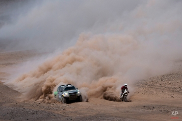Toyota driver Yazeed Alrajhi, from Saudi Arabia, and co-pilot Timo Gottschalk, from Germany, left, overtake KTM motorcyclist Damien Udry, from Switzerland, during the ninth stage of the Dakar Rally between the cities of Iquique and Calama, Chile, Tuesday, Jan. 13, 2015. (AP Photo/Felipe Dana)