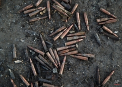 Ammunition abandoned by retreating Ukrainian forces lies on the road near the village of Lohvynove, outside Debaltseve, Ukraine, Sunday, Feb. 22, 2015, on the edge of the territory controlled by Russia-backed separatists. (AP Photo/Vadim Ghirda)