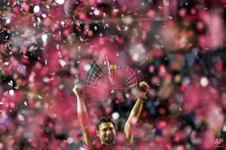 David Ferrer of Spain holds up his trophy after defeating Fabio Fognini of Italy 6-2, 6-3 in the Rio Open tennis tournament men's final match, in Rio de Janeiro, Brazil, Sunday, Feb. 22, 2015. (AP Photo/Felipe Dana)