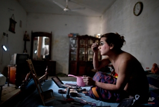 In this Saturday, Jan. 10, 2015 photo, Pakistani Waseem Akram, 27, applies makeup on his face using natural light due to a power cut, as he prepares himself for a party at a friend's place in Rawalpindi, Pakistan. By day, Akram sells mobile phone accessories from an alleyway shop in an old neighborhood of this Pakistani city. But by night, Akram stands before a mirror, shaving away his beard and picking through mascara and rouge to become Rani, a female wedding party dancer. (AP Photo/Muhammed Muheisen)