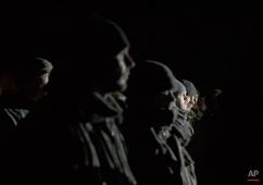 Ukrainian prisoners of war wait in formation before a prisoner exchange in Russia-backed separatist controlled territory, near Zholobok, Ukraine, Saturday, Feb. 21, 2015. (AP Photo/Vadim Ghirda)