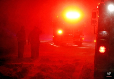 Firefighters stand in wind-driven snow on the coast in Scituate, Mass., Tuesday, Jan. 27, 2015. (AP Photo/Michael Dwyer)