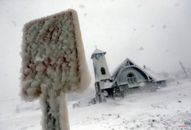 Frozen sea spray coats a road sign and a church during a winter storm in Marshfield, Mass., Tuesday, Jan. 27, 2015. The storm punched out a section of the seawall in the coastal town, police said. (AP Photo/Michael Dwyer)