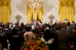 As people in the crowd take cell phone photographs, President Barack Obama, back left, smiles at first lady Michelle Obama as they host a reception in recognition of African American History Month in the East Room of the White House Washington, Thursday, Feb. 26, 2015, (AP Photo/Jacquelyn Martin)