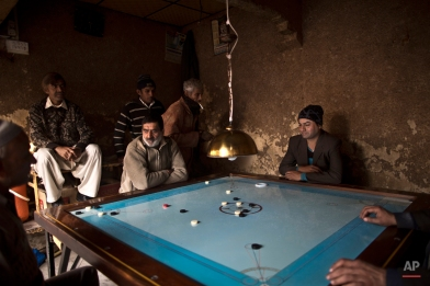 In this Sunday, Jan. 11, 2015, photo, Pakistani Waseem Akram, 27, center, plays a game with neighboring workers at a market in Rawalpindi, Pakistan. By day, Akram sells mobile phone accessories from an alleyway shop in an old neighborhood of this Pakistani city. But by night, Akram stands before a mirror, shaving away his beard and picking through mascara and rouge to become Rani, a female wedding party dancer (AP Photo/Muhammed Muheisen)