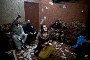 """In this Thursday, Jan. 15, 2015 photo, Pakistani Waseem Akram, 27, dances during a private party in Rawalpindi, Pakistan. By day, Akram sells mobile phone accessories from an alleyway shop in an old neighborhood of this Pakistani city. But by night, he stands before a mirror, shaving away his beard and picking through mascara and rouge to become Rani, a female wedding party dancer. """"Being a dancer at weddings, parties and private events ... helps me earn much more money than working in a shop,"""" Akram said. (AP Photo/Muhammed Muheisen)"""