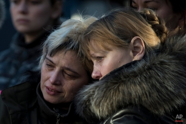 Relatives and members of a Ukrainian military medical unit mourn for their four comrades killed near Debaltseve during a ceremony in Artemivsk, eastern Ukraine, Monday, Feb. 23, 2015. (AP Photo/Evgeniy Maloletka)