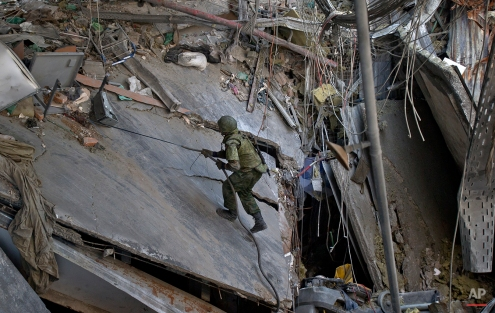 A Russia-backed separatist uses a cable to climb inside the airport terminal while supervising Ukrainian prisoners of war removing bodies of Ukrainian servicemen from the rubble of the airport building outside Donetsk, Ukraine, Wednesday, Feb. 25, 2015. (AP Photo/Vadim Ghirda)