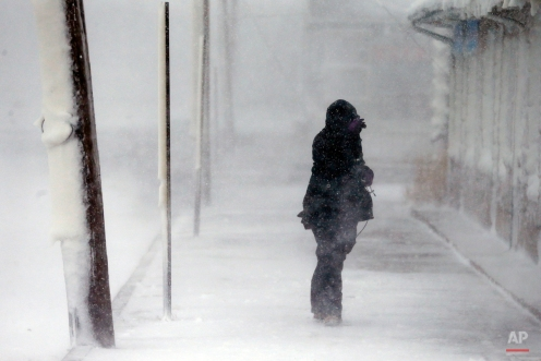 A woman braces against the wind during a winter storm in Marshfield, Mass., Tuesday, Jan. 27, 2015. The storm punched out a section of the seawall in the coastal town of Marshfield, police said. (AP Photo/Michael Dwyer)