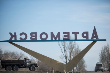 A Ukrainian multiple rocket launcher and a military truck are transported by a sign of the town Artemivsk, eastern Ukraine, Monday, Feb. 23, 2015. (AP Photo/Evgeniy Maloletka)