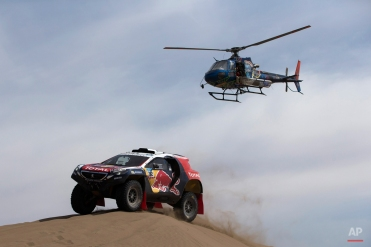 A Dakar helicopter flies over Peugeot driver Stephane Peterhansel and co-pilot Jean Paul Cottret, both of France, as they race through the dunes during the ninth stage of the Dakar Rally 2015 between the cities of Iquique and Calama, Chile, Tuesday, Jan. 13, 2015. (AP Photo/Felipe Dana)