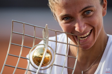 Sara Errani of Italy celebrates biting her trophy after defeating Anna Schmiedlova of Slovakia 7-6, 6-1, in the final match of the Rio Open tennis tournament in Rio de Janeiro, Brazil, Sunday, Feb. 22, 2015. (AP Photo/Felipe Dana)