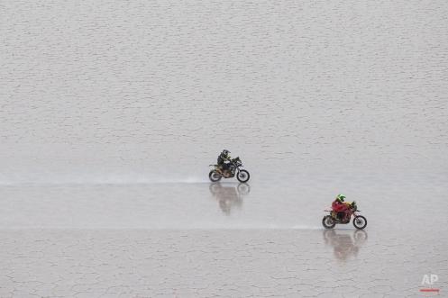 Honda rider Jean de Azevedo of Brazil, right, leads Yamaha rider Michael Metge of France, as they race across the Uyuni salt flat during the eighth stage of the Dakar Rally 2015 between Uyuni, Bolivia, and Iquique, Chile, Monday, Jan. 12, 2015. (AP Photo/Felipe Dana)