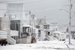 Dexter Newcomb begins cleanup at his house in Scituate, Mass., Wednesday, Jan. 28, 2015, the day after a winter storm left his neighborhood coated in frozen sea spray and sand. (AP Photo/Michael Dwyer)