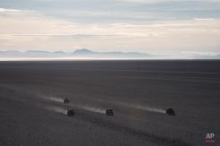 Competitors race across the Uyuni salt flats during the eighth stage of the Dakar Rally 2015 between Uyuni, Bolivia, and Iquique, Chile, Sunday, Jan. 11, 2015. (AP Photo/Felipe Dana)