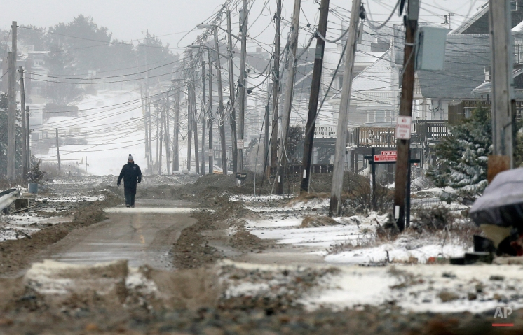 A man walks on a portion of road cleared of sand washed up by ocean waves during a winter storm in the Humarock section of Scituate, Mass., Tuesday, Jan. 27, 2015. (AP Photo/Michael Dwyer)