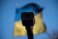A Ukrainian flag is seen behind a canon near the village of Luhanske, eastern Ukraine, Tuesday, Feb. 24, 2015. (AP Photo/Evgeniy Maloletka)