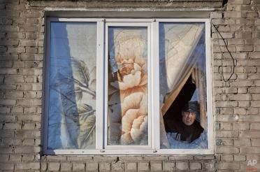 A resident peers from behind a blanket affixed to a window frame behind broken panes at an apartment in Debaltseve, Ukraine, Monday, Feb. 23, 2015. After weeks of relentless fighting, the embattled Ukrainian rail hub of Debaltseve fell last week to Russia-backed separatists. (AP Photo/Vadim Ghirda)