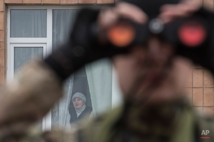 A Ukrainian serviceman watches through binoculars positions of pro-Russian rebels as a local woman looks from a window in the village of Chermalyk, eastern Ukraine, Thursday, Feb. 26, 2015. In a long-awaited development, Ukrainian forces and separatist fighters both announced Thursday they are pulling back heavy weapons from the front line in eastern Ukraine. (AP Photo/Evgeniy Maloletka)