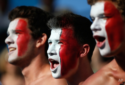 Face painted fans show their support to Richard Gasquet of France as he plays South Africa's Kevin Anderson during their third round match at the Australian Open tennis championship in Melbourne, Australia, Friday, Jan. 23, 2015. (AP Photo/Vincent Thian)