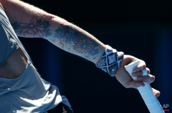 The tattoo on the arm of Bethanie Mattek-Sands of the U.S. is seen as she plays Simona Halep of Romania during their third round match at the Australian Open tennis championship in Melbourne, Australia, Friday, Jan. 23, 2015. (AP Photo/Rob Griffith)