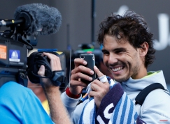 Rafael Nadal of Spain uses a smartphone to take a picture of a TV camera after defeating Kevin Anderson of South Africa in their fourth round match at the Australian Open tennis championship in Melbourne, Australia, Sunday, Jan. 25, 2015. (AP Photo/Vincent Thian )